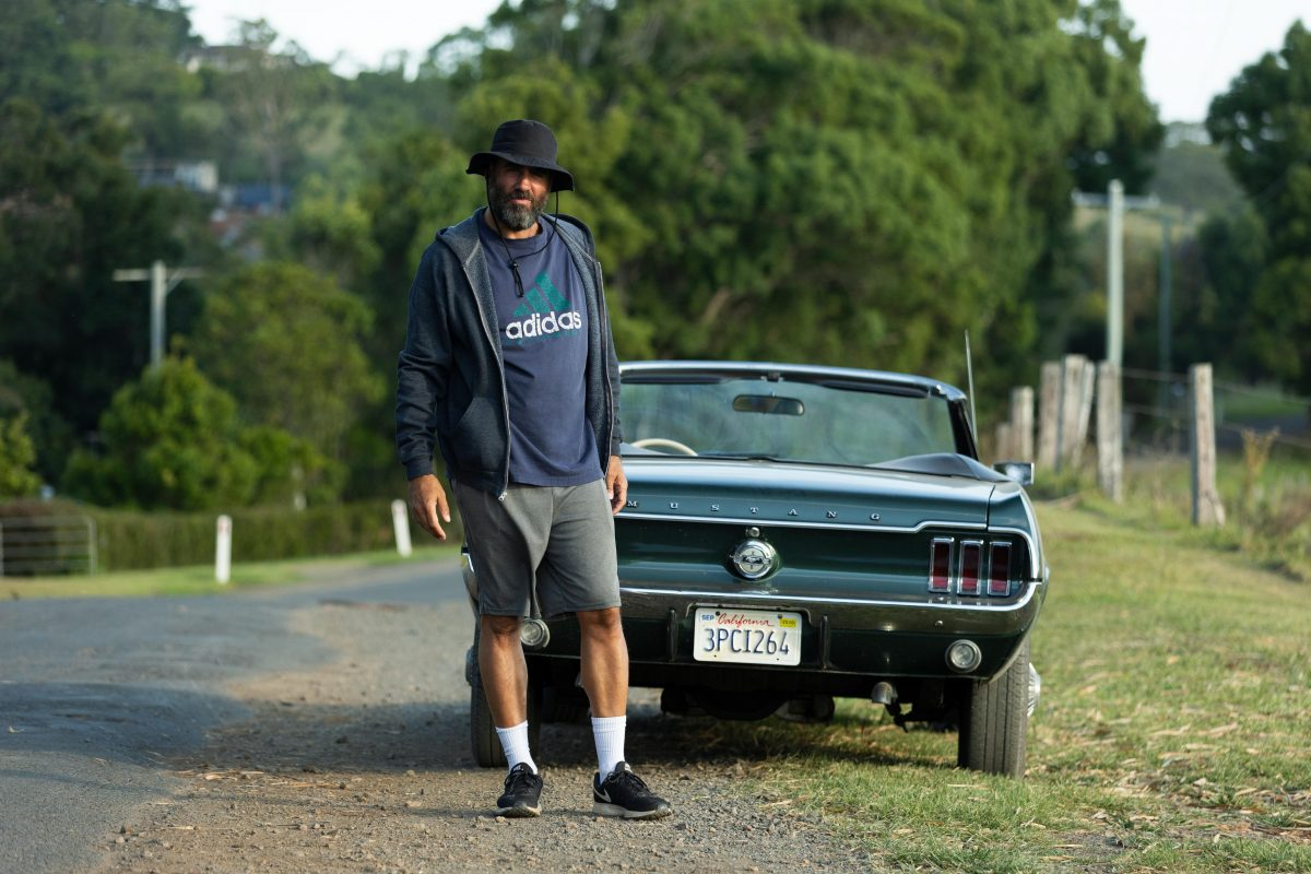 Tony Hogburn stands outside his car wearing an Adidas t-shirt and wide-brimmed hat.