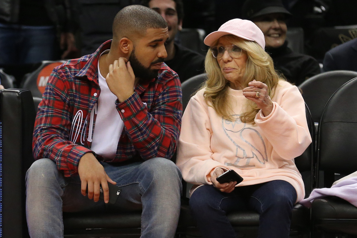 Drake and Sandi Graham sit court side in a red and grey plaid shirt and a blush ovo sweat shirt at the Toronto Raptors vs Cleveland Cavaliers game.