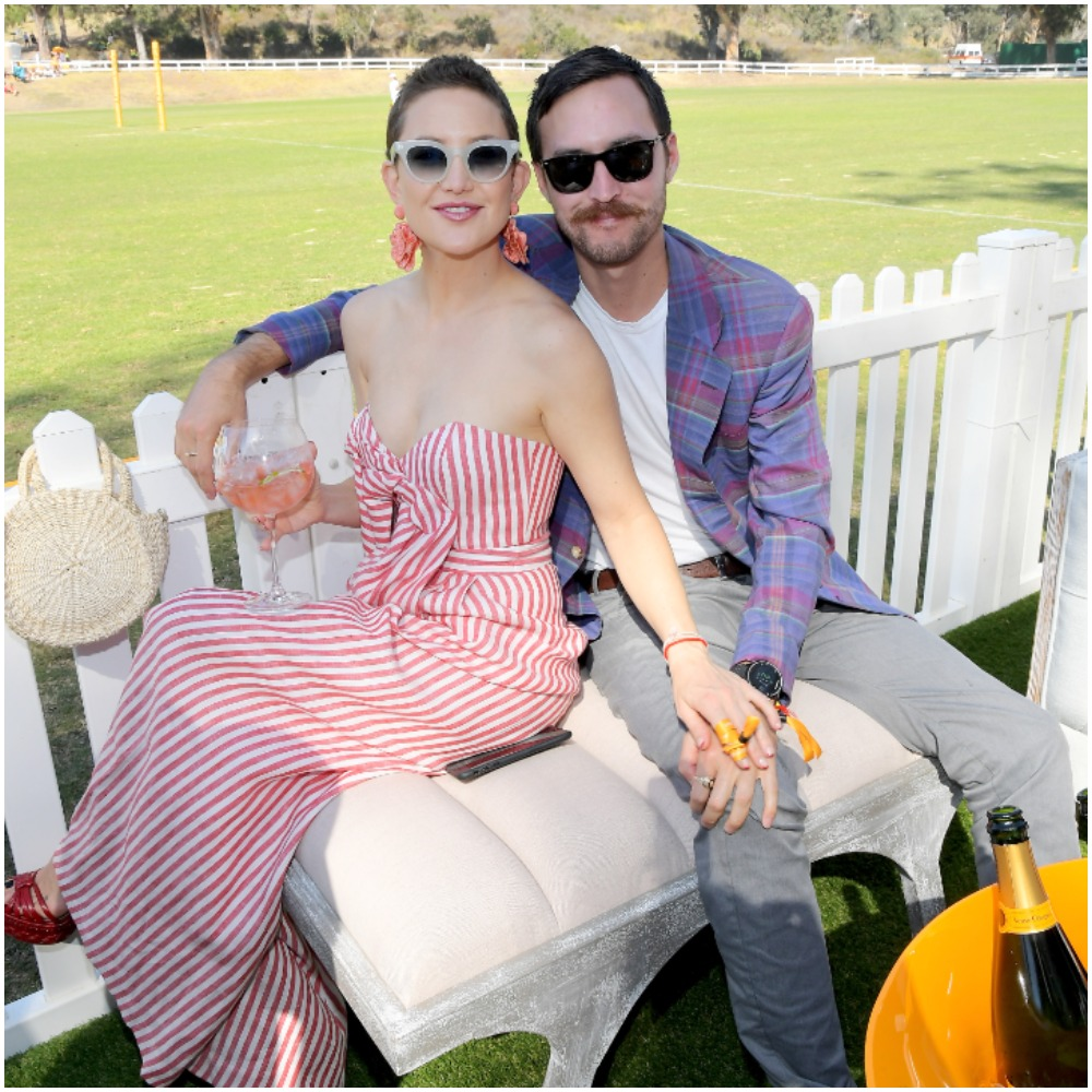 Kate Hudson and Danny Fujikawa attending the Eighth Annual Veuve Clicquot Polo Classic wearing a striped dress and patterned blazer.