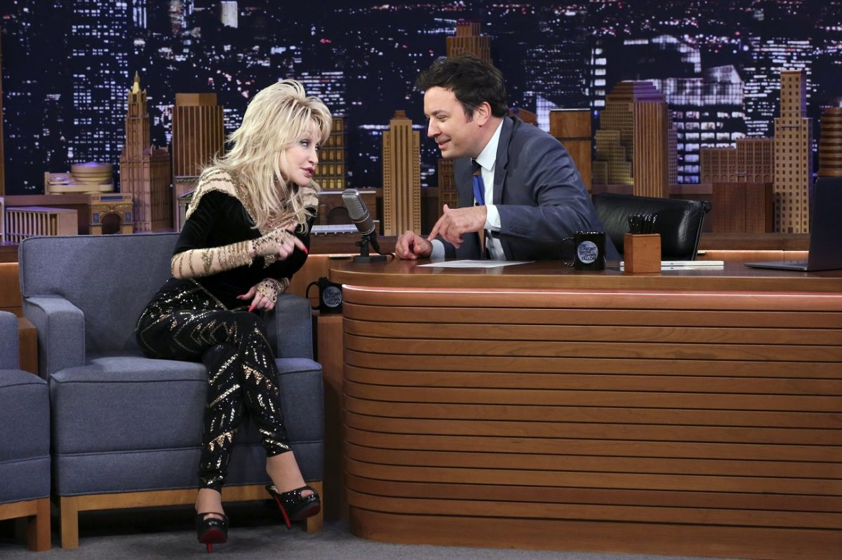 Dolly Parton in a black outfit and Jimmy Fallon in a suit talk to one another on 'The Tonight Show with Jimmy Fallon.