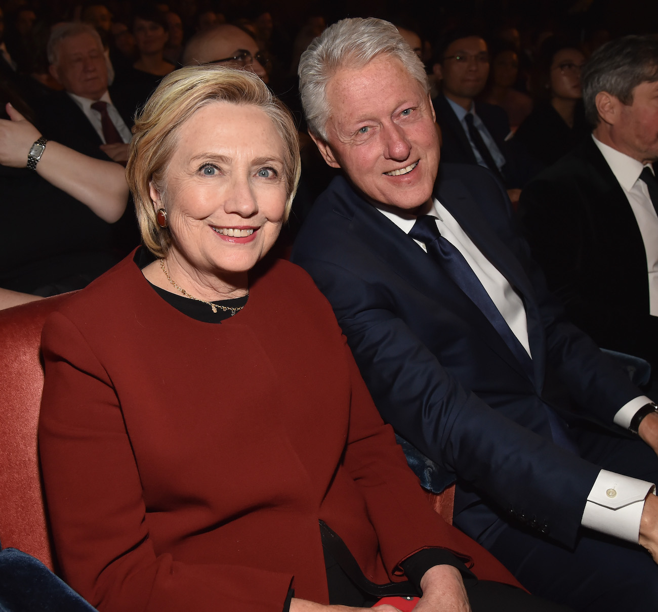 Hillary Clinton and Bill Clinton smile as they sit together at the 2018 Grammy Awards