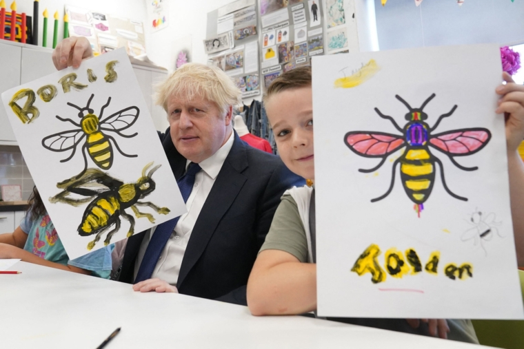 Britain's Prime Minister Boris Johnson holds up his Manchester Bee painting next to Jayden in an art class during a visit to the HideOut Youth Zone on the morning of the first day of the annual Conservative Party Conference being held at the Manchester Central convention centre in Manchester, north-west England on October 3, 2021. (Photo by Stefan Rousseau / POOL / AFP) (Photo by STEFAN ROUSSEAU/POOL/AFP via Getty Images)