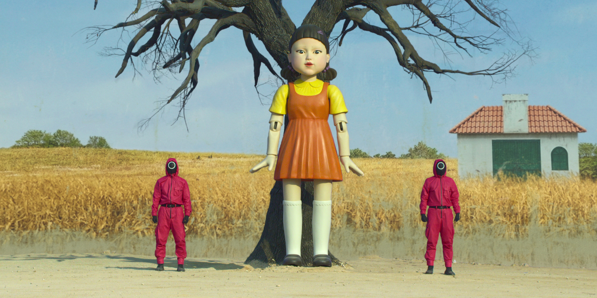 Two workers in pink jumpsuits stand beside the 'Squid Game' doll in episode 1.