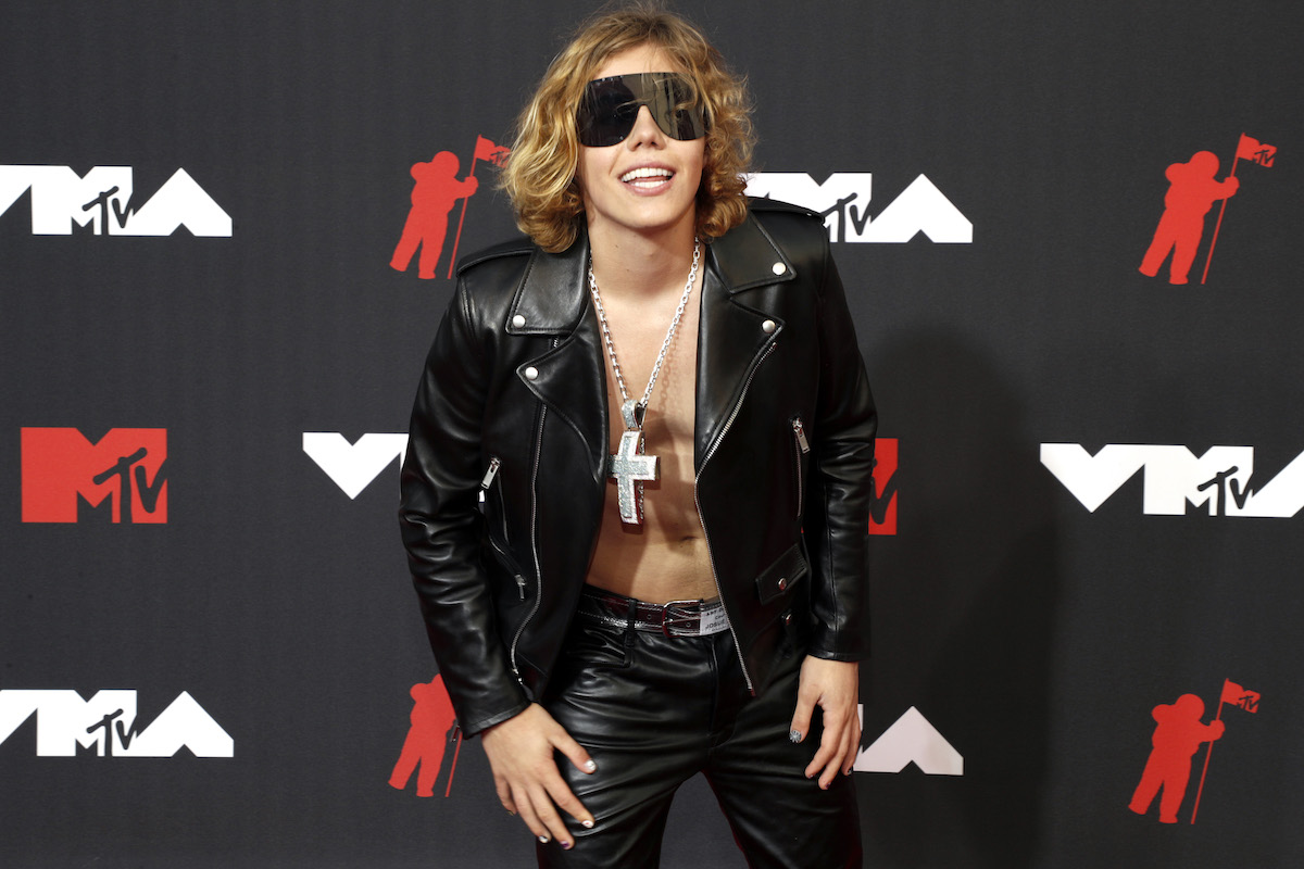 The Kid Laroi wears dark sunglasses and goes shirtless underneath a black leather jacket at an event.