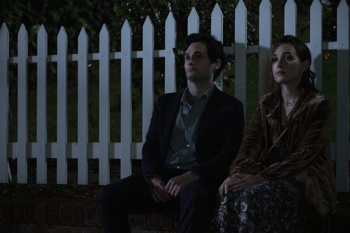 Penn Badgley and Victoria Pedretti, 'You' Season 3 cast members, sitting next to each other outside in the dark